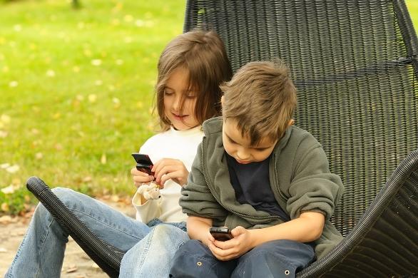 Två barn i en stol leker med sina mobiltelefoner.